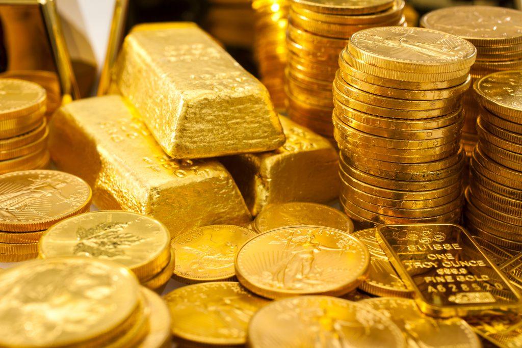 Золотые слитки и монеты в хранилище.