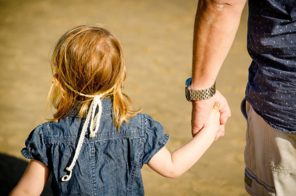 мужчина ведет за руку девочку