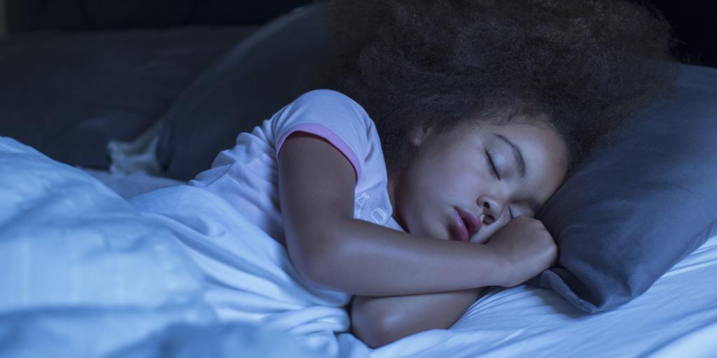 Девочка спит в своей постели.
