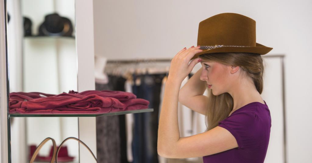 Девушка примеряет шляпу.