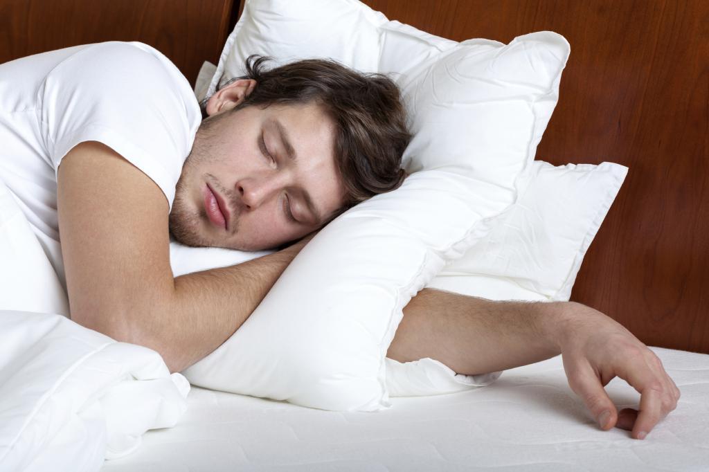 Мужчина спит на подушках