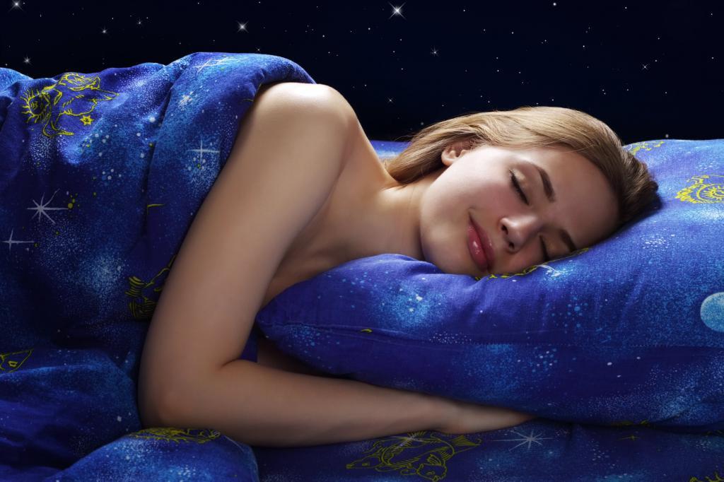 Красивая девушка спит под одеялом
