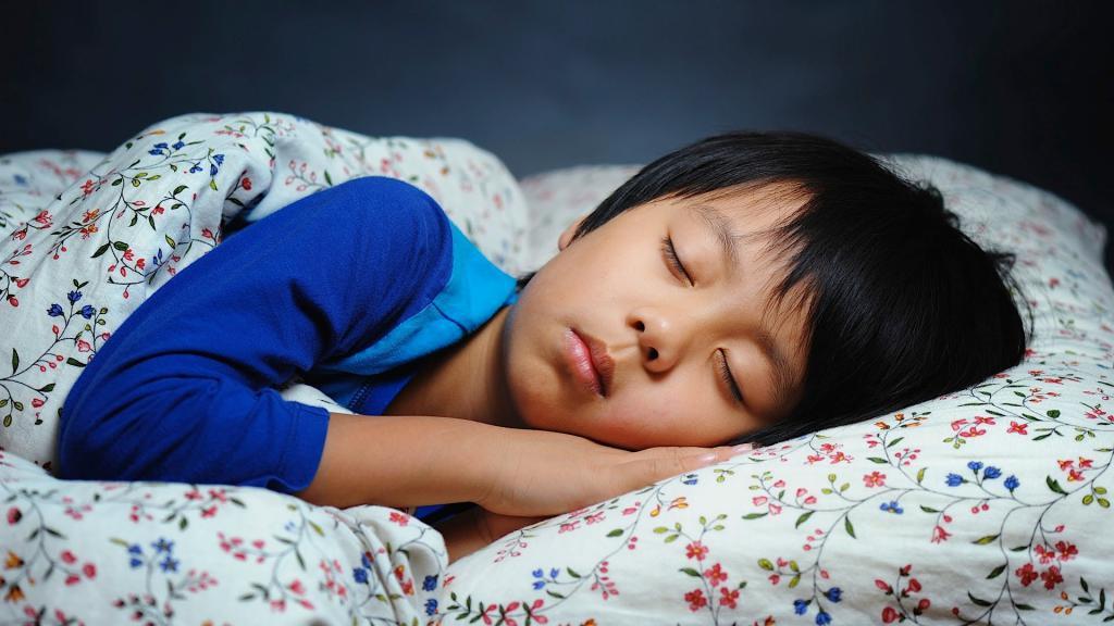 Мальчик спит у себя в кроватке