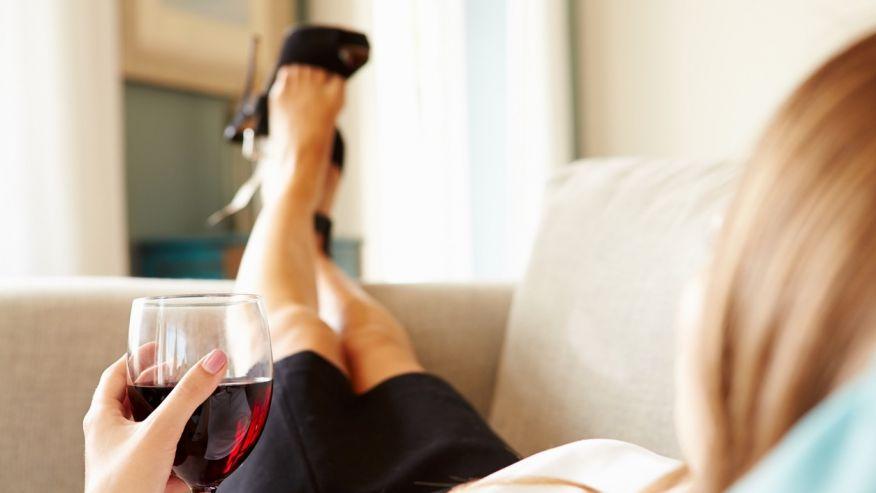 женщина пьет вино на диване