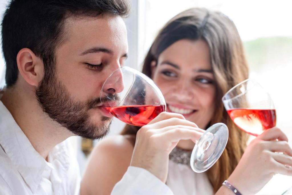 мужчина и женщина пьют вино из фужеров