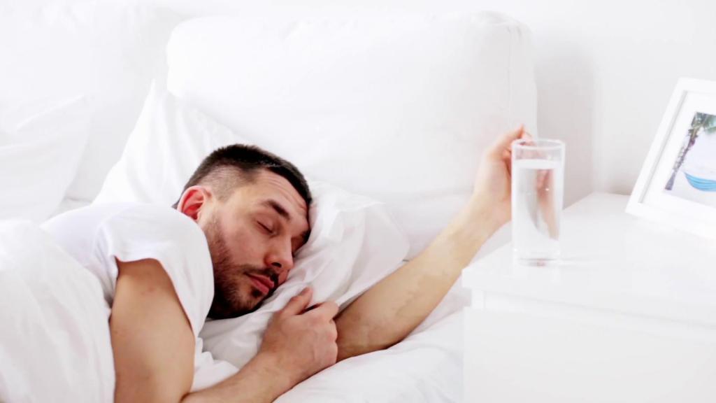 мужчина спит, а рядом стакан воды