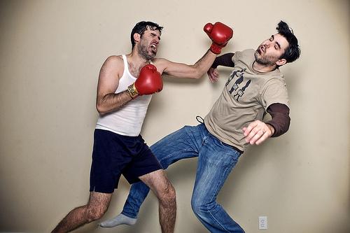 Мужчина избивает приятеля в боксерских перчатках.
