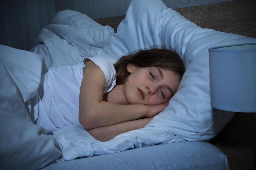 Девочка спит в своей кровати.