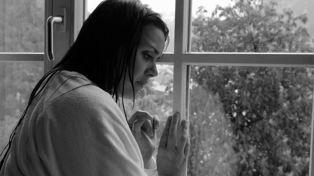 Девушка плачет у окна.