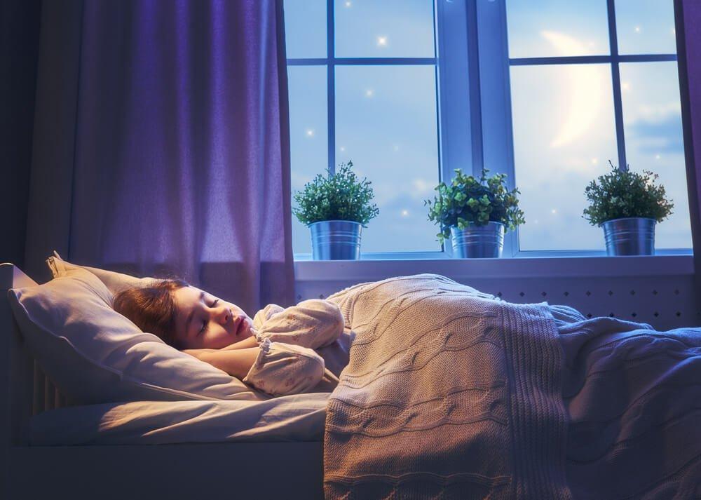 Девочка спит в своей комнате.