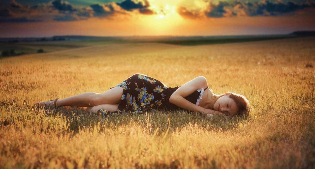 Девушка спит в поле.