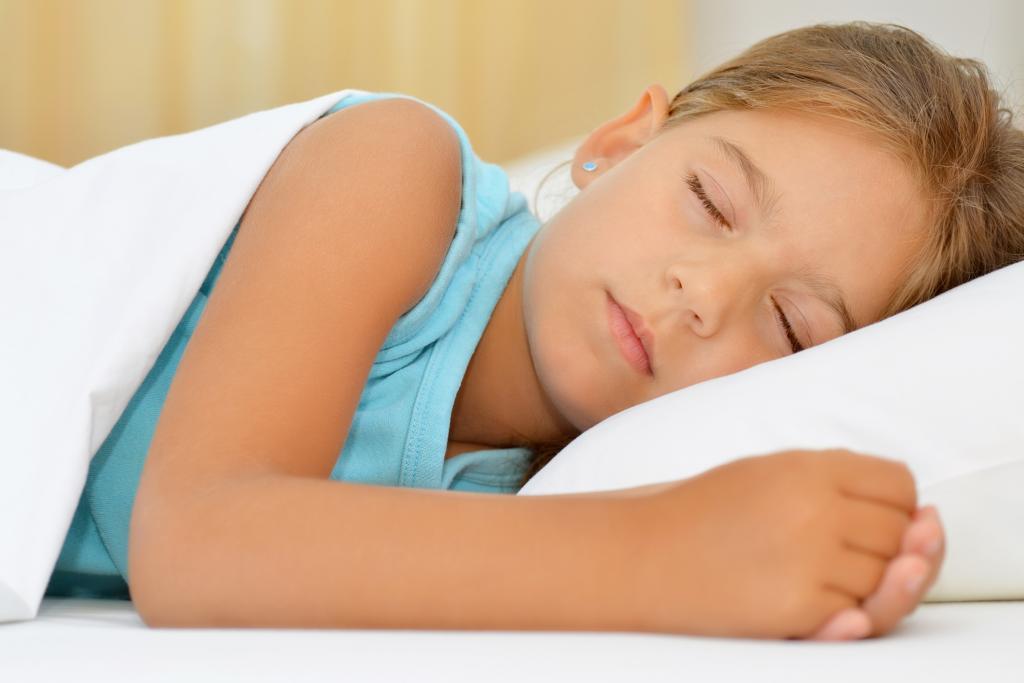 Девочка спит в кровати.