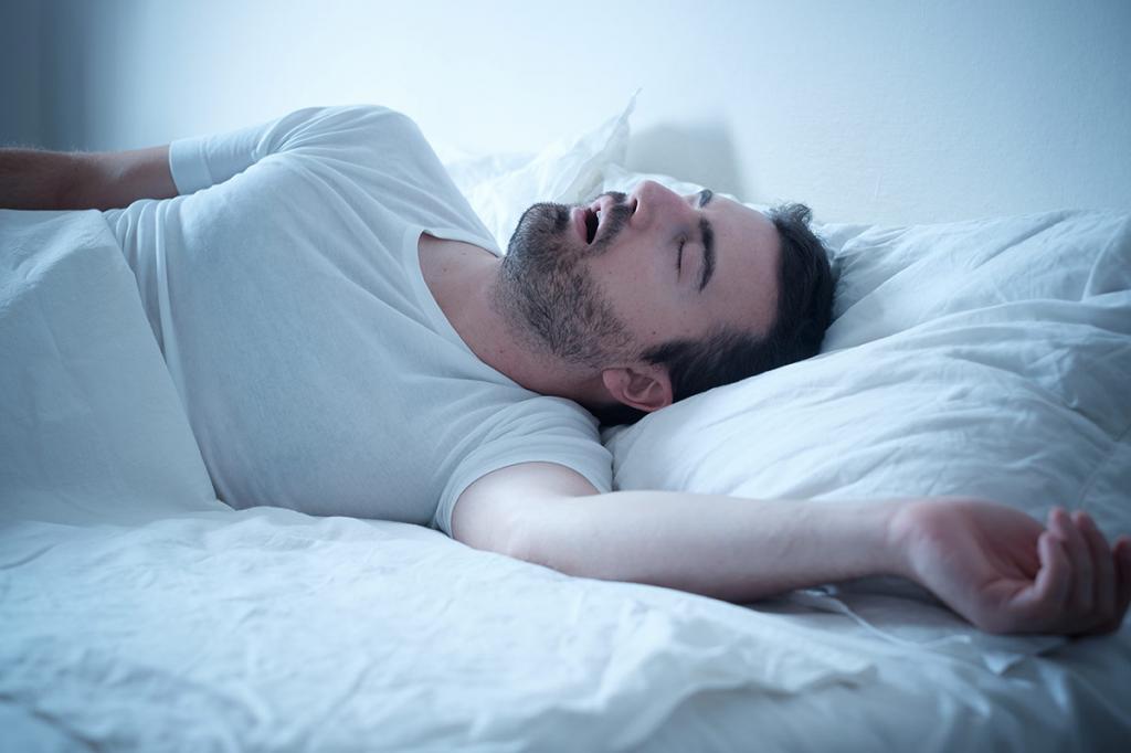 Мужчина спит в постели.