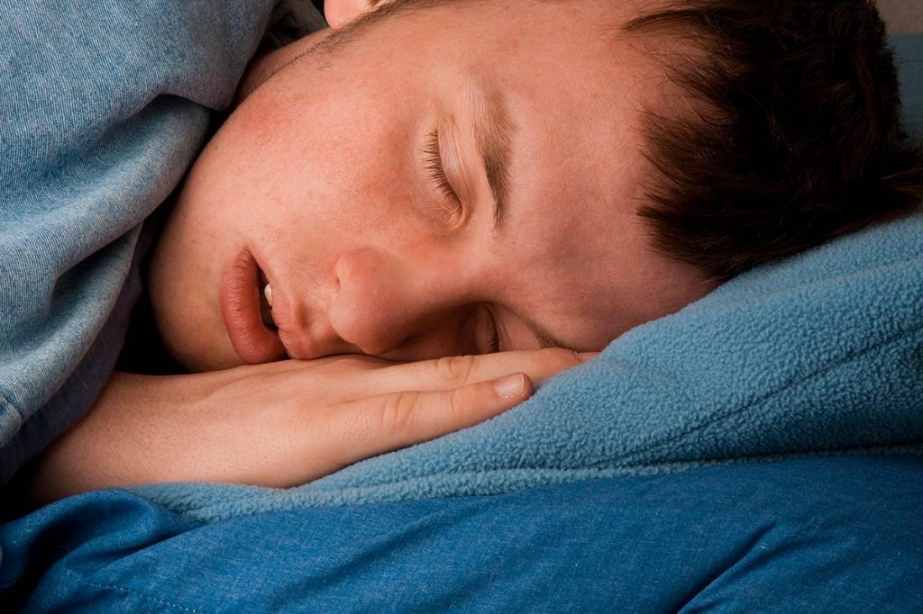 Мужчина спит в кровати.