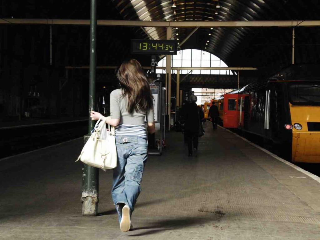 Девушка пытается догнать поезд.