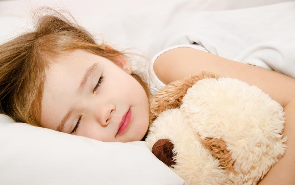 Девочка спит с собакой.